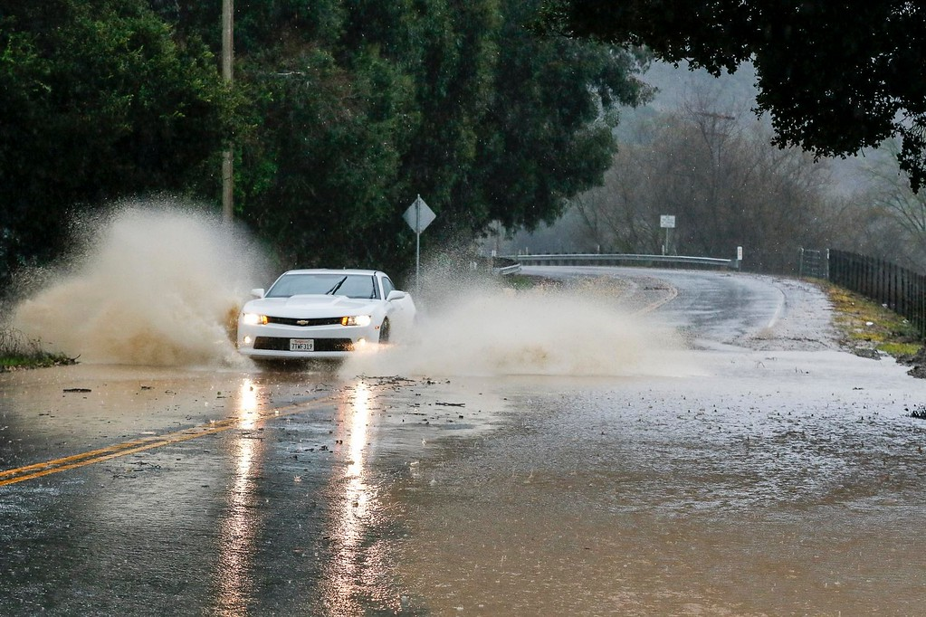 . A motorist drives through a flood on Crazyhorse Canyon Rd. during a downpour of rain on Sunday, January 8, 2017 in Salinas, Calif. (Vernon McKnight/Herald Correspondent)