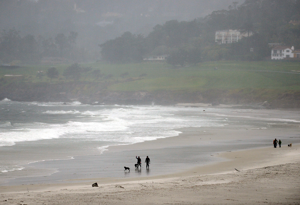 . People and their dogs brave the weather on Carmel Beach as a large storm brings strong winds and rain to Monterey County on Sunday January 8, 2017. (David Royal - Monterey Herald)
