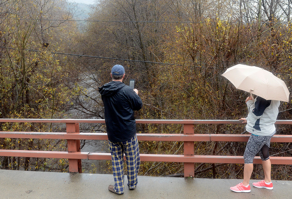 . People gather to shoot photos as the Carmel River flows heavy below the Robinson Canyon Road bridge in Carmel Valley as a large storm brings strong winds and rain to Monterey County on Sunday January 8, 2017. (David Royal - Monterey Herald)
