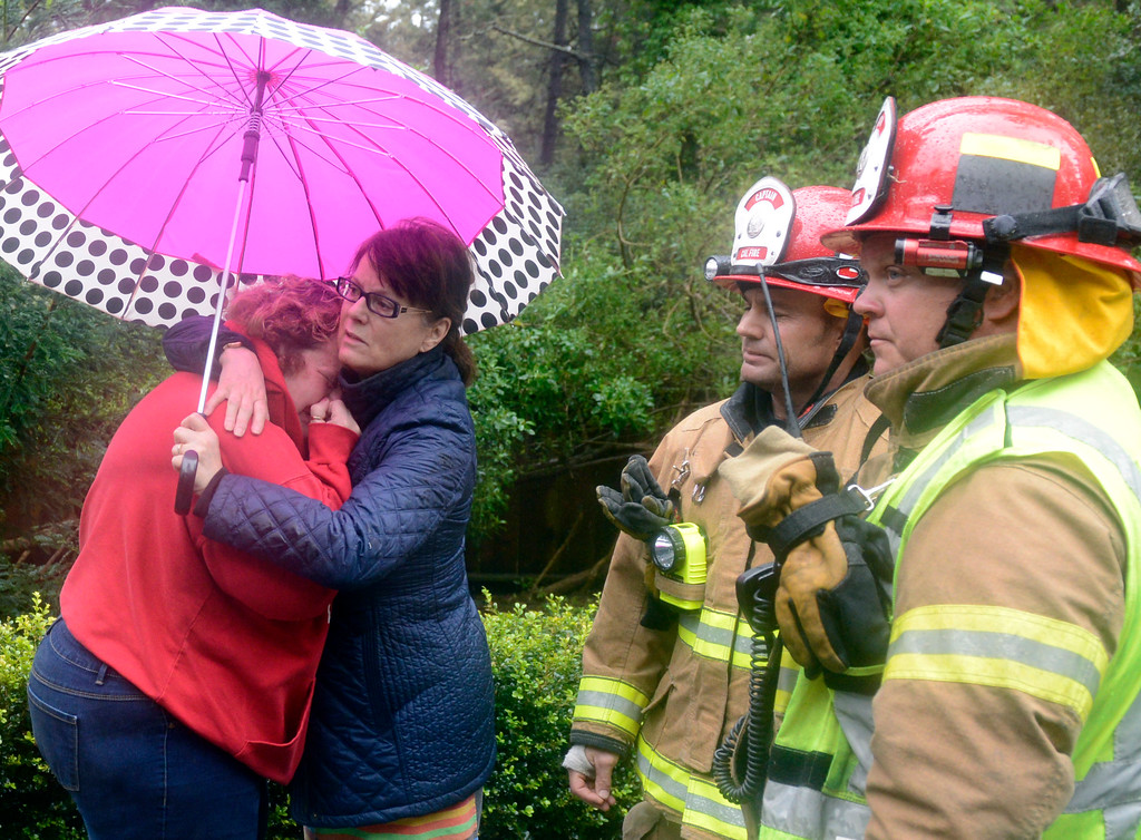 . Dorothy Maras, left, is comforted by neighbor Dominique Gallet-Shanklin after a large pine tree fell on her house on Crest Road in Pebble Beach as a storm brings strong winds and rain to Monterey County on Sunday January 8, 2017. Calfire captians are at right. (David Royal - Monterey Herald)