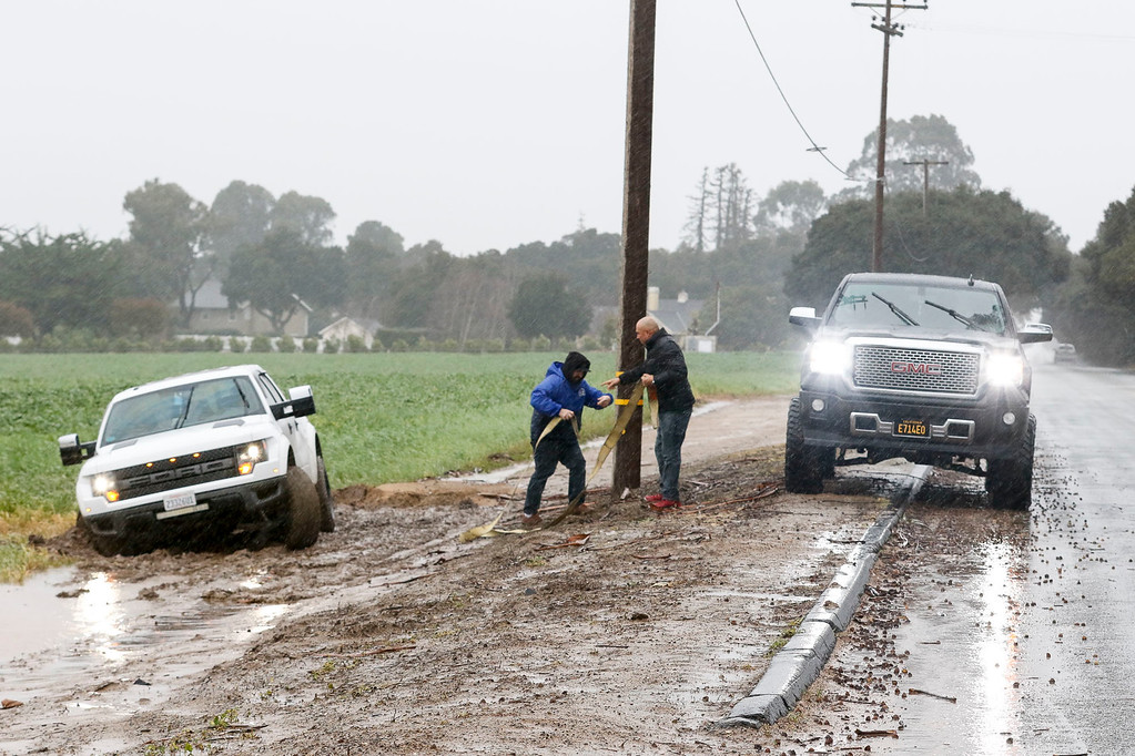 . A motorist stuck in the mud in a field on San Juan Grade Rd. gets help from another motorist, right, during a downpour of rain on Sunday, January 8, 2017 in Salinas, Calif. (Vernon McKnight/Herald Correspondent)