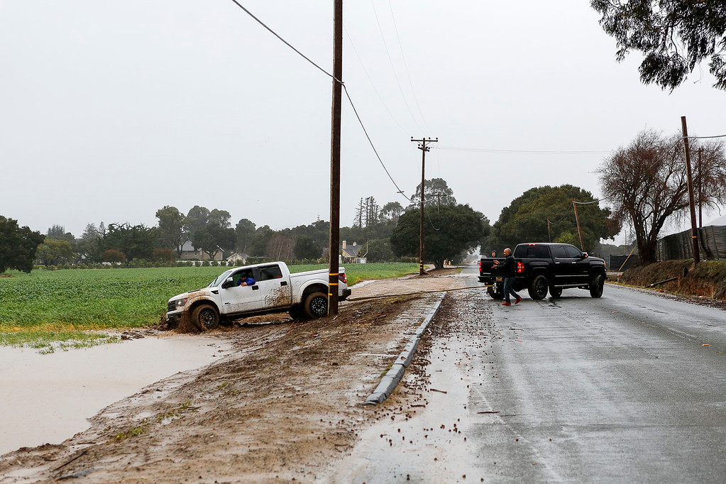 . A motorist stuck in a field on San Juan Grade Rd. gets pulled out of the mud by another motorist, right, during a downpour of rain on Sunday, January 8, 2017 in Salinas, Calif. (Vernon McKnight/Herald Correspondent)