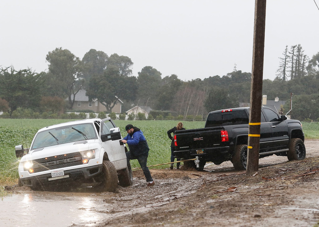 . A motorist stuck in the mud in a field on San Juan Grade Rd. jumps back into his truck as he gets help from another motorist during a downpour of rain on Sunday, January 8, 2017 in Salinas, Calif. (Vernon McKnight/Herald Correspondent)