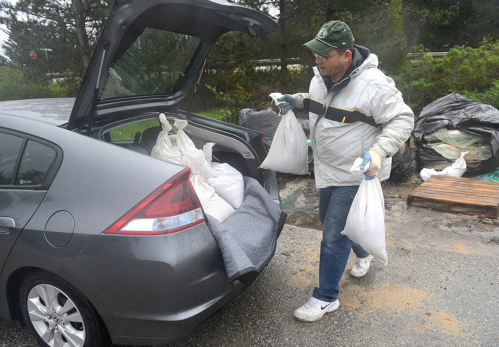 . Bruce Suckow loads sandbags into the back of his car near the Carmel River Inn as a large storm brings strong winds and rain to Monterey County on Sunday January 8, 2017. (David Royal - Monterey Herald)