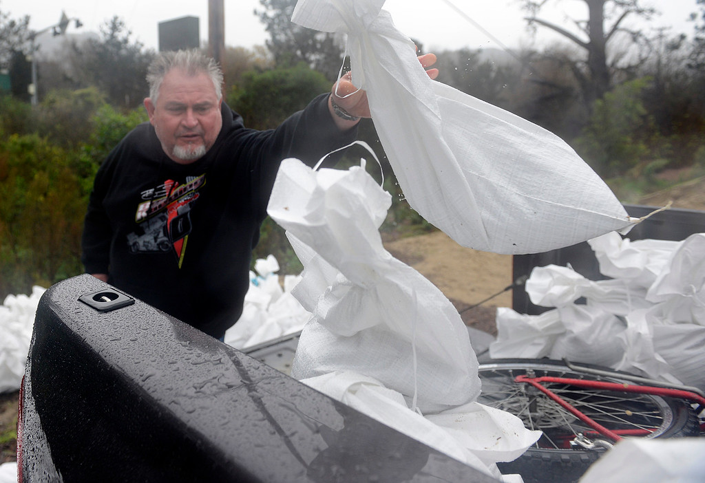 . Steve Markley loads sandbags into the back of his truck near the Carmel River Inn as a large storm brings strong winds and rain to Monterey County on Sunday January 8, 2017. (David Royal - Monterey Herald)