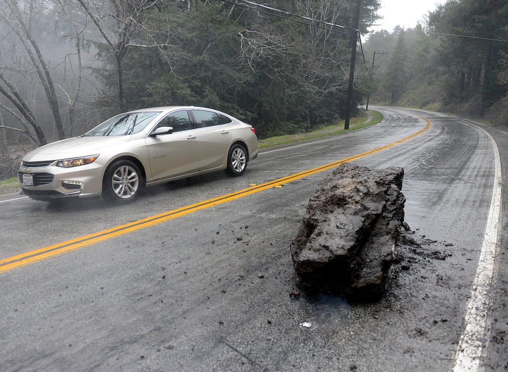 . A car passes a large boulder which fell onto the northbound lane of Highway 1 near St. Francis Church in Big Sur as a new storm rolls into Monterey County on Tuesday February 7, 2017. (David Royal - Monterey Herald)