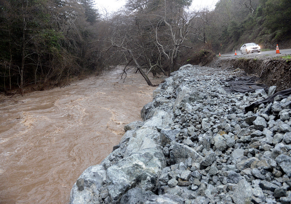 . The Big Sur Rver flows heavy as a car passes an area where rocks were piled along Highway 1 to control erosion in Big Sur as a new storm rolls into Monterey County on Tuesday February 7, 2017. (David Royal - Monterey Herald)