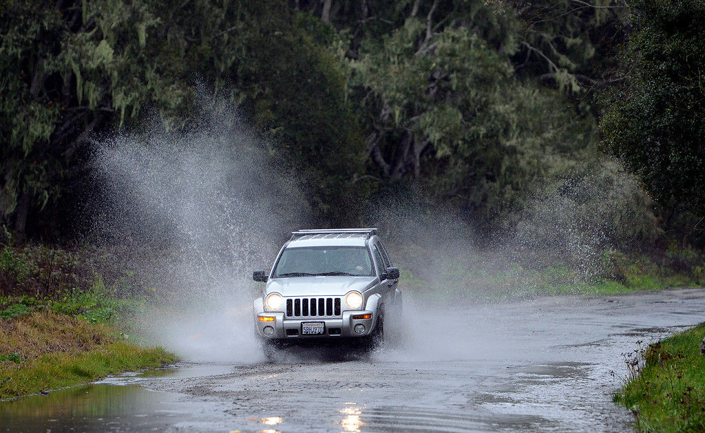 . An SUV throws spray as it drives on flooded Iris Canyon Road in Monterey as a new storm rolls into Monterey County on Tuesday February 7, 2017. (David Royal - Monterey Herald)