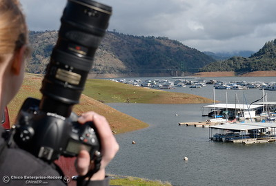 Department of Water Resources Photographer Kelly Grow looks for her next shot as she takes pictures of the rising lake levels at Lake Oroville near the Bidwell Canyon Marina in Oroville, Calif. Wed. Jan 11, 2017. (Bill Husa -- Enterprise-Record)