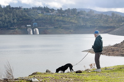 """Local resident Merrill Beck and his dog Lucy enjoy a walk near the Spillway Launch Facility at Lake Oroville in Oroville Calif. Wed. Jan 11, 2017. Beck said  """"It's amazing how fast it goes up and it goes down just as quickly. I think it has gone up 80 or 90' since this whole thing started."""" (Bill Husa -- Enterprise-Record)"""