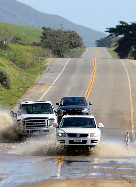 . Trucks drive through flooding on Highway 1 in Big Sur on Wednesday February 22, 2017. (David Royal - Monterey Herald)