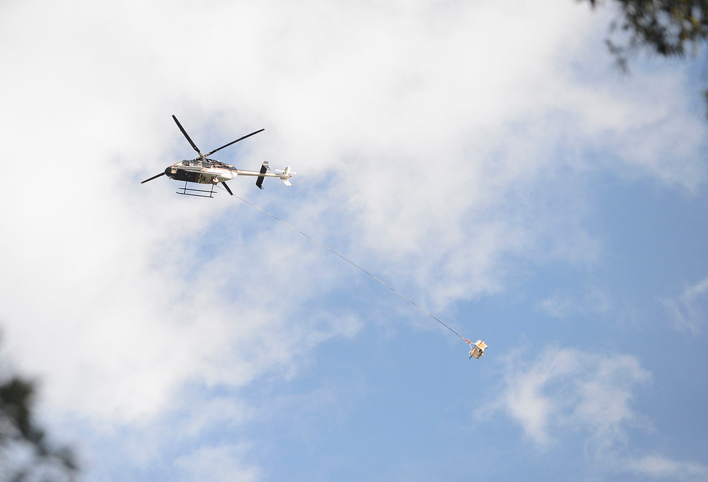 . A helicopter flies over the village of Big Sur with a basket attached on Wednesday February 22, 2017. (David Royal - Monterey Herald)