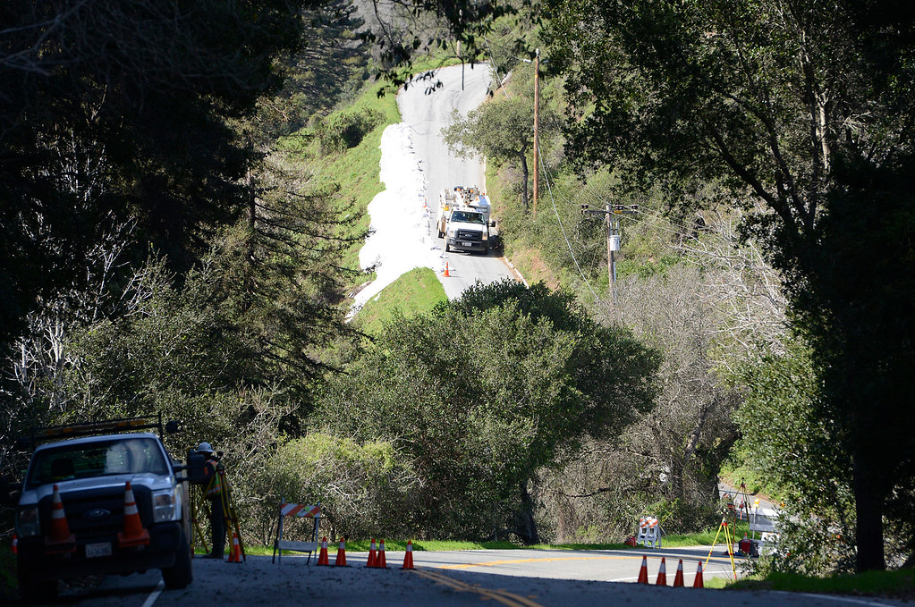. A utility truck drives past a hillside covered with tarps on Pfeiffer Ridge Road as crews work on storm damage on Highway 1in Big Sur on Wednesday February 22, 2017. (David Royal - Monterey Herald)