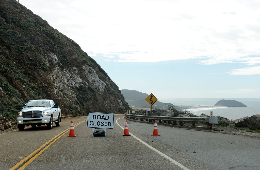 . A California State Parks vehicle passes a road close sign on Hurricane Point above heavy landslides in Big Sur on Wednesday February 22, 2017. (David Royal - Monterey Herald)