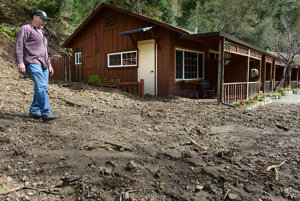 . Big Sur River Inn general manager Rick Aldinger walks on the remains of a mud slide that slumped down onto the inn\'s motel rooms on the east side of Highway 1 in Big Sur on Wednesday February 22, 2017. (David Royal - Monterey Herald)