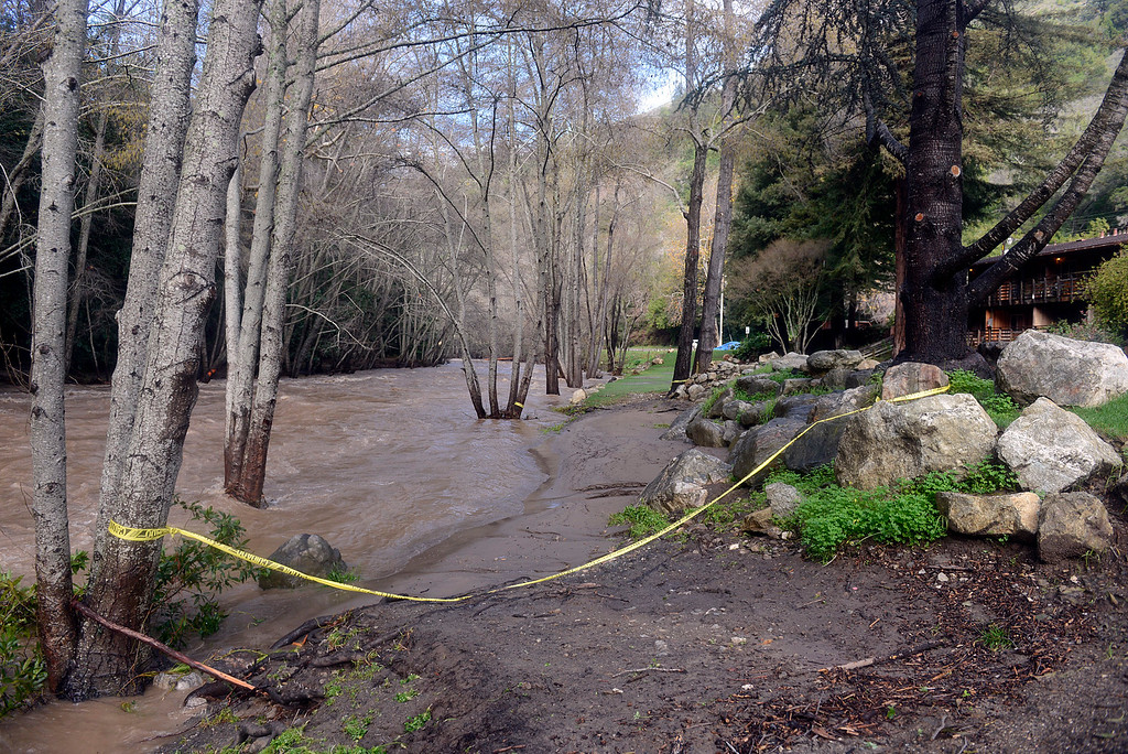 . Caution tape hangs between trees and rocks on the banks of the surging Big Sur River behind The River Inn in Big Sur on Monday January 9, 2017. (David Royal - Monterey Herald)