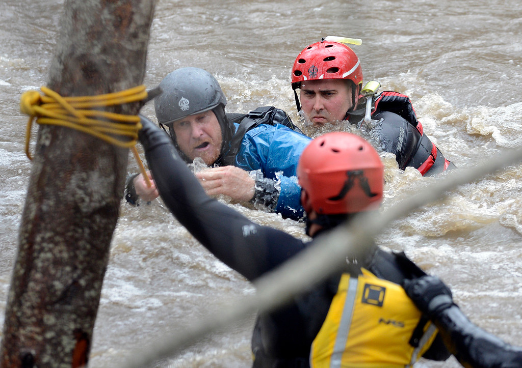 . Jason Williams, left, is rescued by Calfire rescue swimmer Danny Ciecek after Williams got snagged on trees while trying to kayak the Carmel River with a friend near Paso Hondo Road in Carmel Valley on Monday January 9, 2017 after a large storm passed through Monterey County. (David Royal - Monterey Herald)