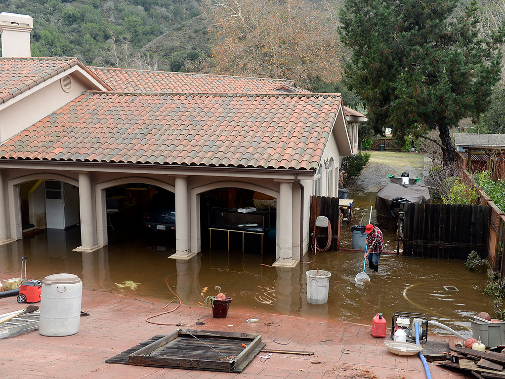. Joe Tringali sifts debris from near a pump draining water from his flooded home after the Carmel River swept over its banks on Paso Hondo Road in Carmel Valley on Monday January 9, 2017 after a large storm passed through Monterey County. (David Royal - Monterey Herald)