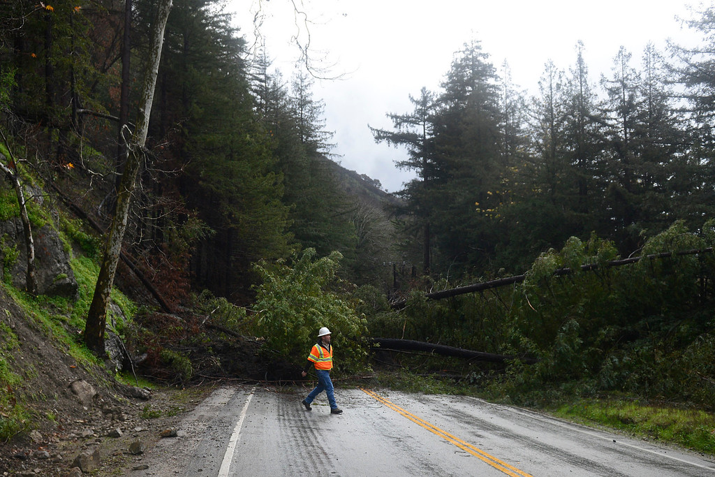 . PG&E trouble man Adam Sissom surveys downed wires at a slide that blocked Highway 1 just south of Fernwood in Big Sur on Monday January 9, 2017 after a large storm passed through Monterey County. The Soberanes Fire scarred the area this past summer. (David Royal - Monterey Herald)