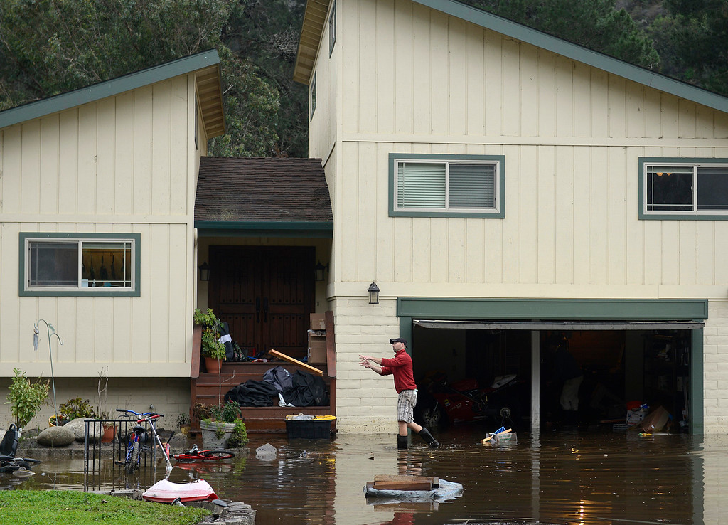 . Garry Briant tosses a piece of lumber while cleaning his flooded home on Paso Hondo Road after the Carmel River swept over its banks in Carmel Valley on Monday January 9, 2017 after a large storm passed through Monterey County. (David Royal - Monterey Herald)
