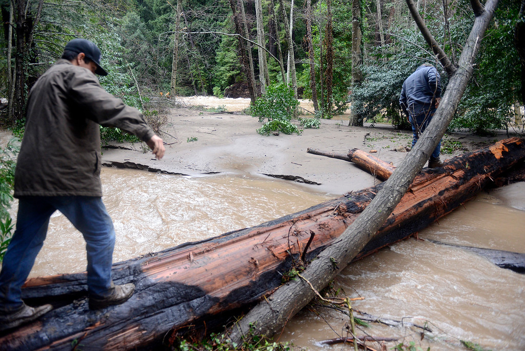 . Dean Cordrey, right and his son Fred, 18, walk across a log straddling a flow of the Big Sur River flow near St. Francis Church in Big Sur on Monday January 9, 2017 after a large storm passed through Monterey County. (David Royal - Monterey Herald)
