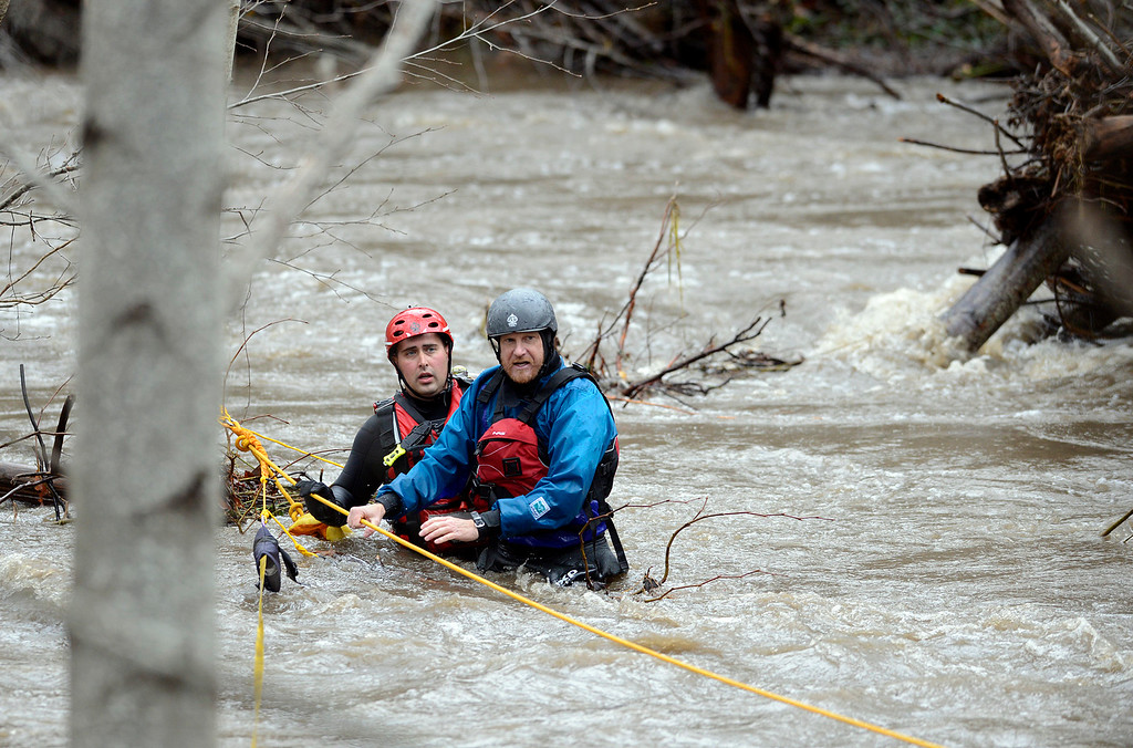 . Jason Williams, right, is rescued by Calfire rescue swimmer Danny Ciecek after Williams got snagged on trees while trying to kayak the Carmel River with a friend near Paso Hondo Road in Carmel Valley on Monday January 9, 2017 after a large storm passed through Monterey County. (David Royal - Monterey Herald)