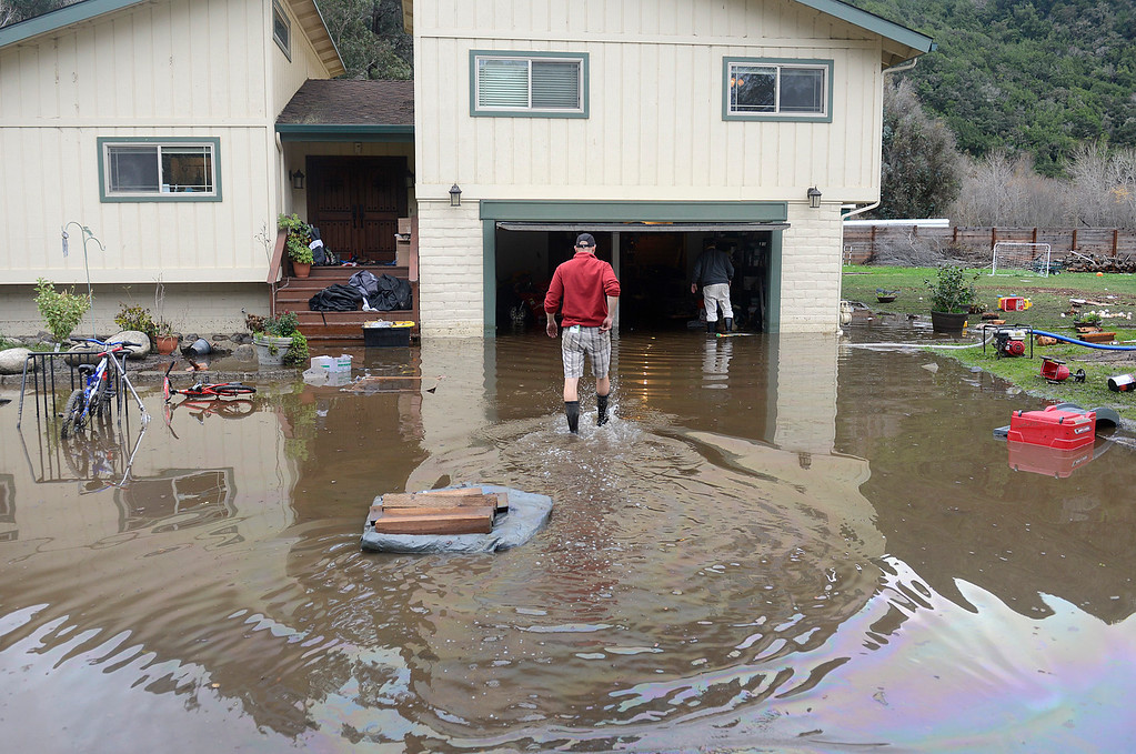 . Garry Briant, left, walks back to his flooded home while cleaning the structure with his father in law Terry McGowan after the Carmel River swept over its banks on Paso Hondo Road in Carmel Valley on Monday January 9, 2017 after a large storm passed through Monterey County. (David Royal - Monterey Herald)