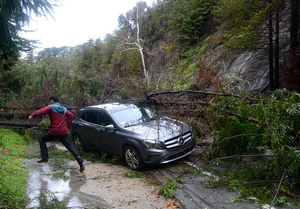 . A man jumps over a water flow near a car smashed by a mudslide on Highway 1 just south of Fernwood in Big Sur on Monday January 9, 2017 after a large storm passed through Monterey County. The drivers of the vehicle were uninjured when the slide came down from the Soberanes Fire burn scar, blocking the highway and knocking out power to the south. (David Royal - Monterey Herald)