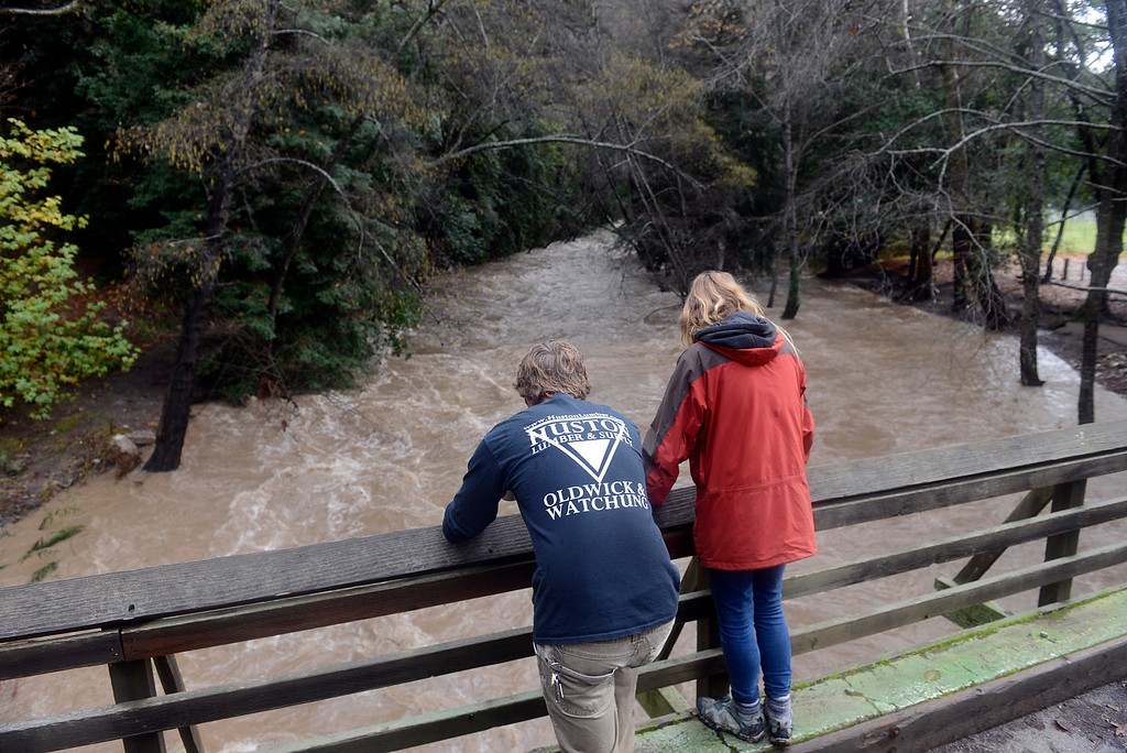. Owen Tansey and his girlfriend Jess watch the Big Sur River flow heavy under a bridge at Fernwood in Big Sur on Monday January 9, 2017 after a large storm passed through Monterey County. (David Royal - Monterey Herald)