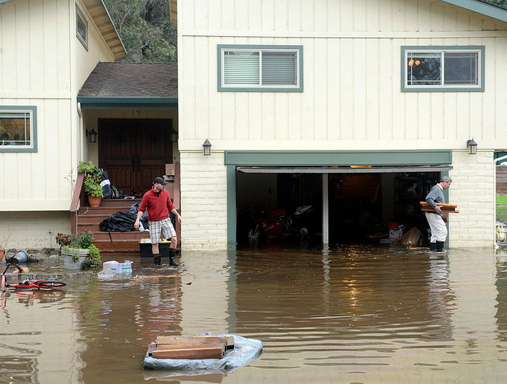 . Garry Briant, left, and his father in law Terry McGowan clean his flooded home on Paso Hondo Road after the Carmel River swept over its banks in Carmel Valley on Monday January 9, 2017 after a large storm passed through Monterey County. (David Royal - Monterey Herald)