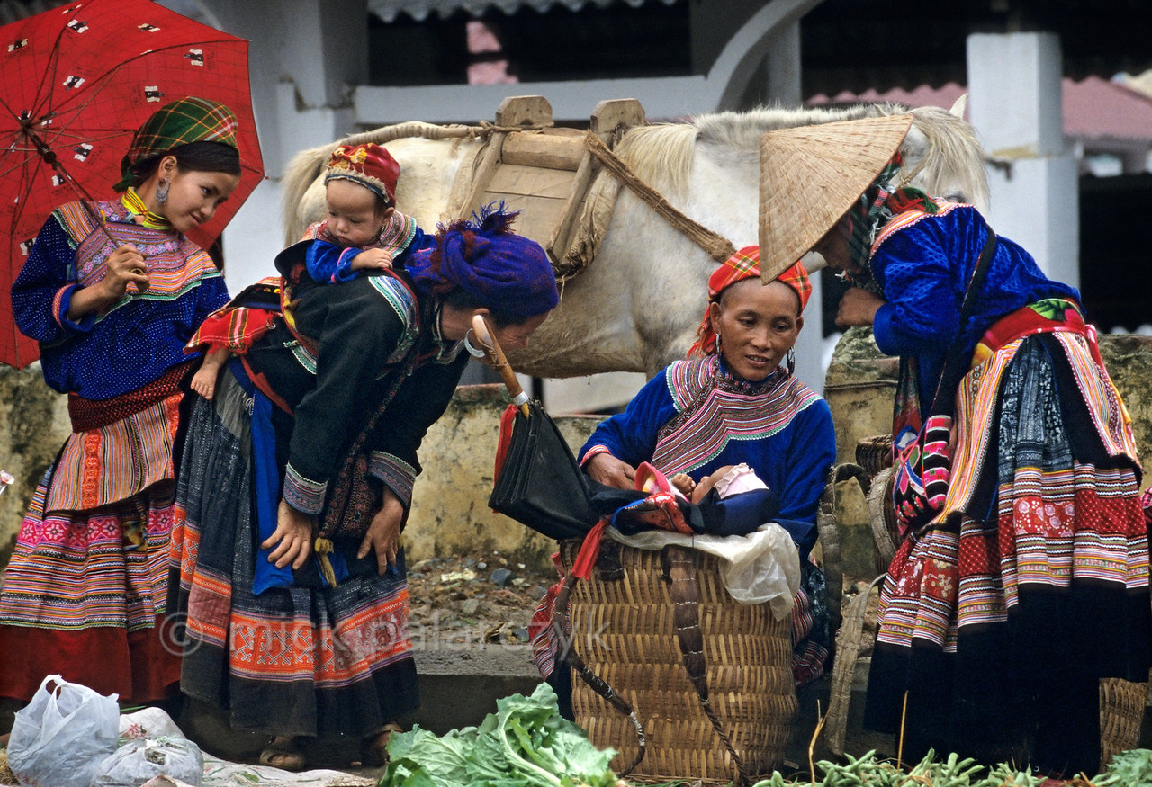[VIETNAM.NORTH 21.533]<br /> 'It's about the baby.'<br /> <br /> Like everywhere else in the world, the baby gets most of the attention, cradled on a basket in the market of Bac Hà. Being a Flower H'mong baby, he will grow up in a world of psychedelic colours, created in textile by his mother, aunts and sisters. Photo Mick Palarczyk
