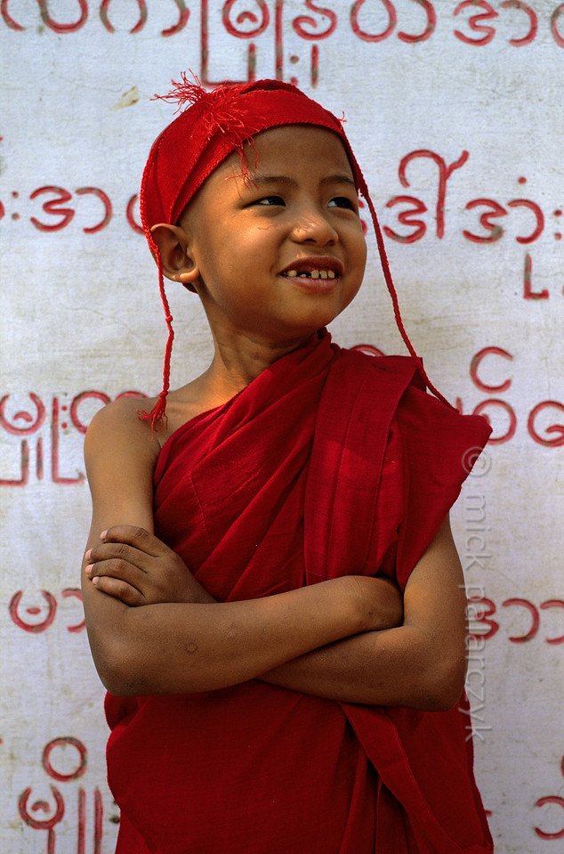 [BURMA 25.036]<br /> 'Young monk at Sagaing.'<br /> <br /> 	This young monk is standing in front of a slab that records the names of people that have donated money to local temples at the foot of Sagaing Hill. Photo Mick Palarczyk.
