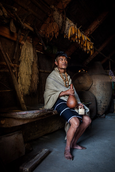 A Chakesang man sits in his morung with a rice beer filled in his mug made of gourd at the Hornbill festival in Nagaland, India