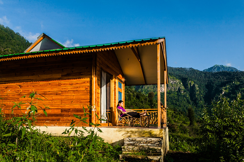 The beautiful wooden cottages soaked in the morning sun at The Goat Village in Raithal en route Dayara Bugyal