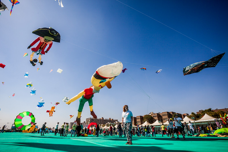A kiteist poses with some awesome kites flying up at the International Kite Festival 2019, Ahmedabad, India