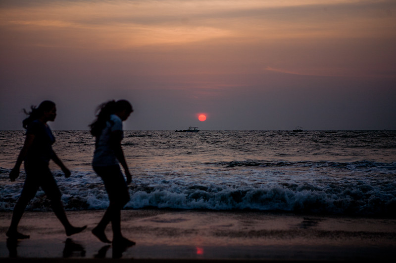 Two girls enjoy a leisure walk as the sun sets at the Baga beach in Goa