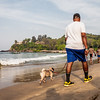 A man walking with his pug in the morning at the Baga beach in Goa