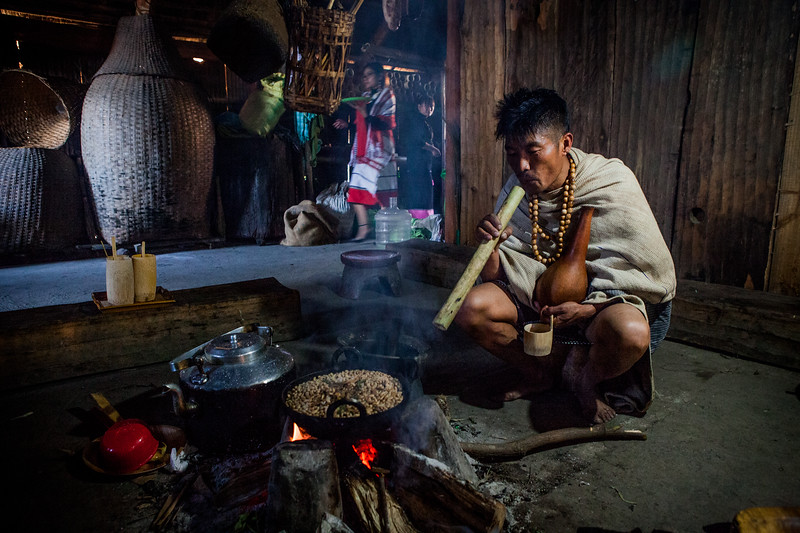 Setting up the fire to roast the Naga beans inside the Chakesang morung at the Hornbill festival in Nagaland, India