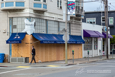 Plump Jack boards up their entire storefront; man seen walking his dog past it.