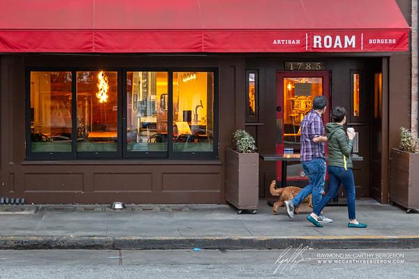 Couple walks past a closed Roam Artisan Burgers while drinking Starbucks coffee.