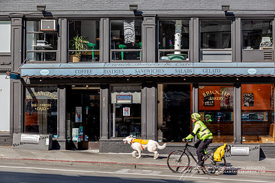 Man riding his bicycle while his dog runs alongside him outside an open Boulangerie.