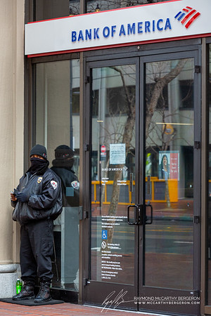 Man stands guard at a Bank of America.