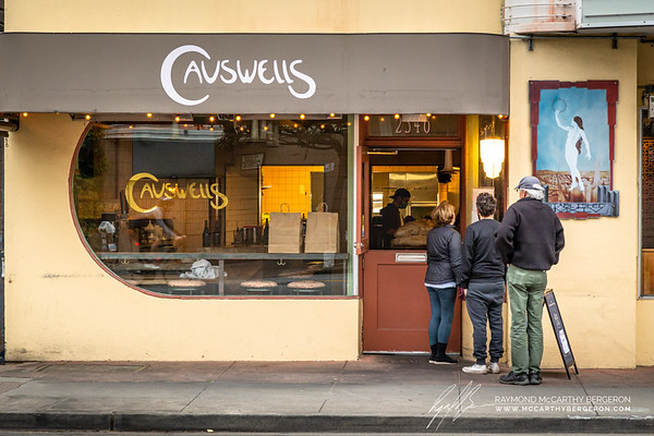 Employees in the kitchen and in front of house of Causwells prepare orders while wearing gloves and masks as guests outside look at the menu posted on the window.
