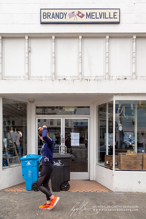 Woman jogs past Brandy Melville which closed their doors during the crisis.
