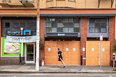 "Jogger passing an old, ""New Happy Hour"" banner that hangs above Sushi In - doing take out only - next to a boarded up local chain Souvla."
