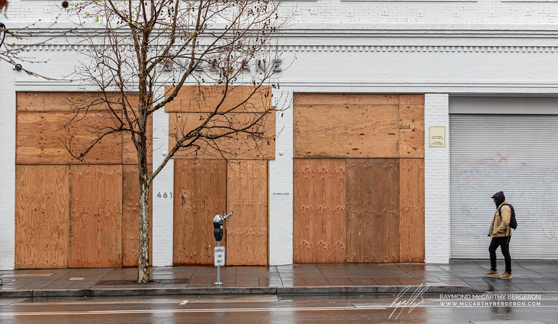Everlane completely boarded up as man walks by.