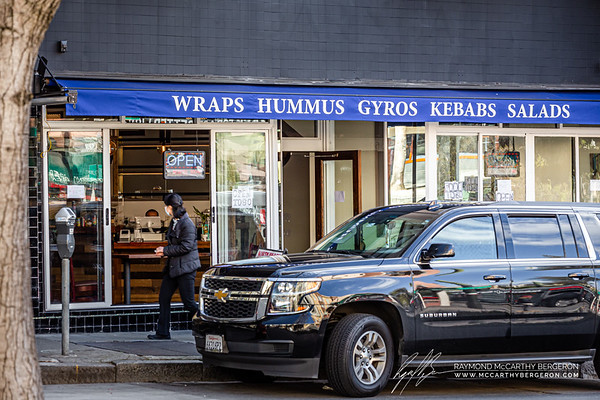 Woman passes by North Beach Gyros with a very bored man sitting behind the register.