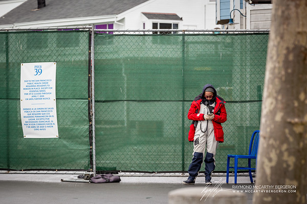 Workers guards the new fencing of Pier 39 while looking at their phone.