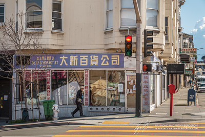Da Xin Linen's Outlet posts signs saying they're closed as man walks by.