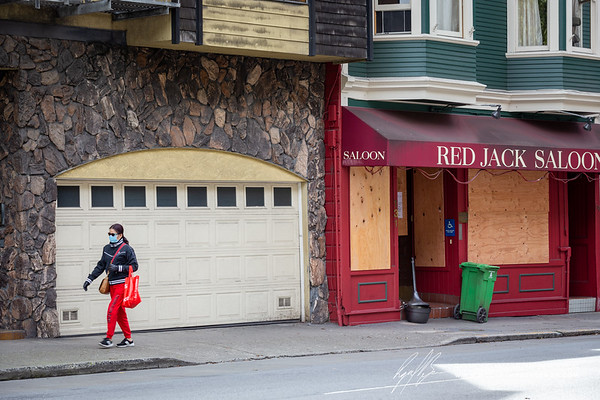 Woman in protective mask and gloves walks past a boarded up Red Jack Saloon.